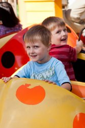Andrew and Will riding the ladybugs at Happy Hollow