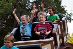 Andrew and Will riding the roller coaster at Happy Hollow 2